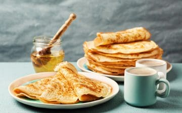 crepes on a plate with honey int he background and a stack of crepes behind