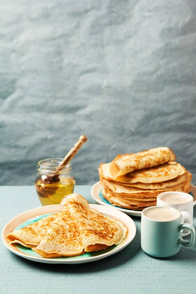 vertical photo of crepes ready to eat with coffee mugs and honey