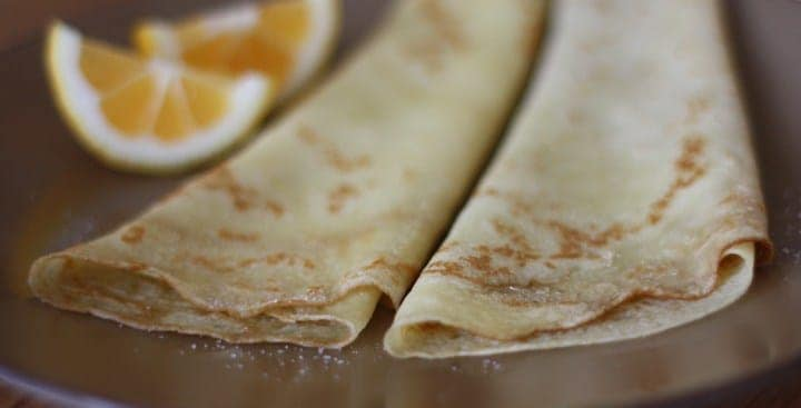 homemade crêpes on a plate with lemon wedges