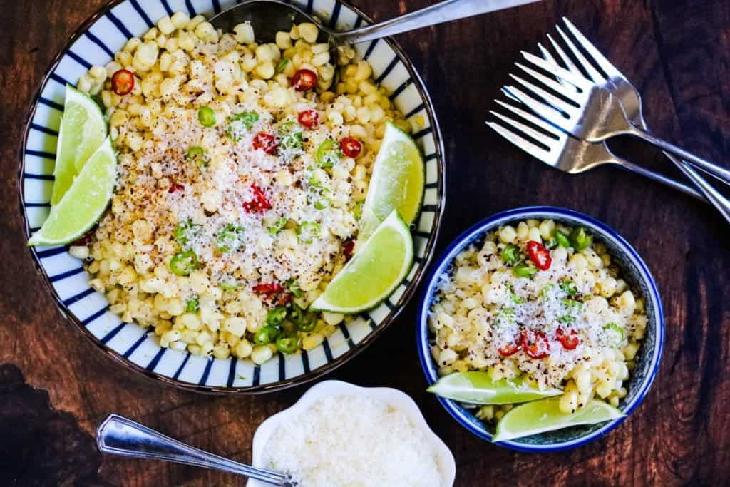 Mexican corn salad with limes, jalapeños, and cheese in bowls ready to eat