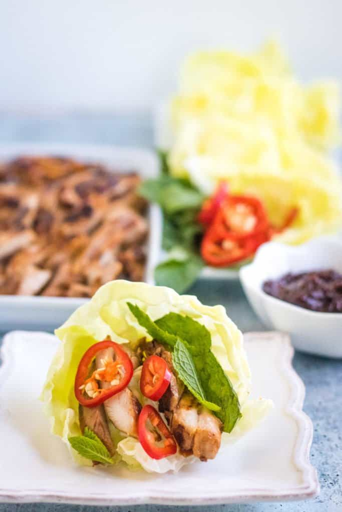 gochujang chicken is wrapped in crisp lettuce leaves with fresh mint and chilies