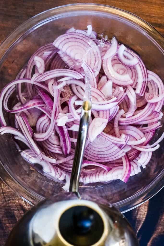 Pouring hot water over sliced red onions for making mexican pickled onions