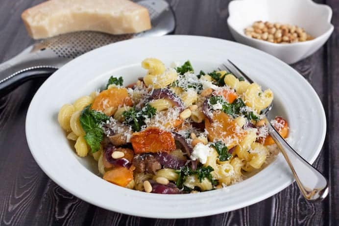pasta with fuyu persimmons and goat cheese in a bowl