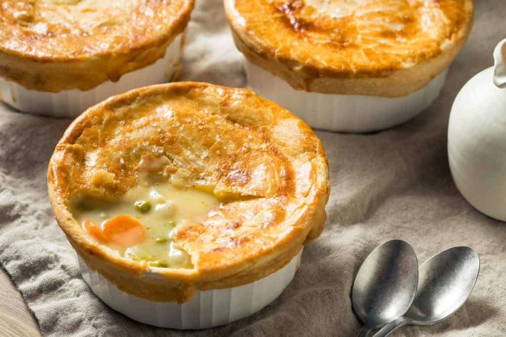 three mini chicken pot pies in white ramekins, shot from a low angle.