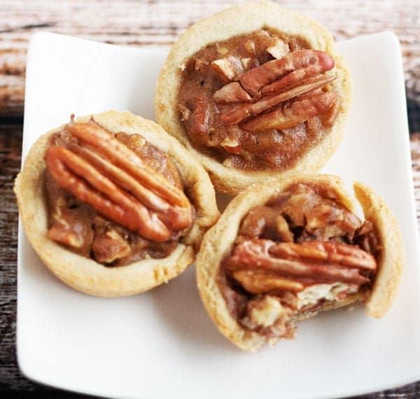three gluten free pecan pie tartlets on a plate