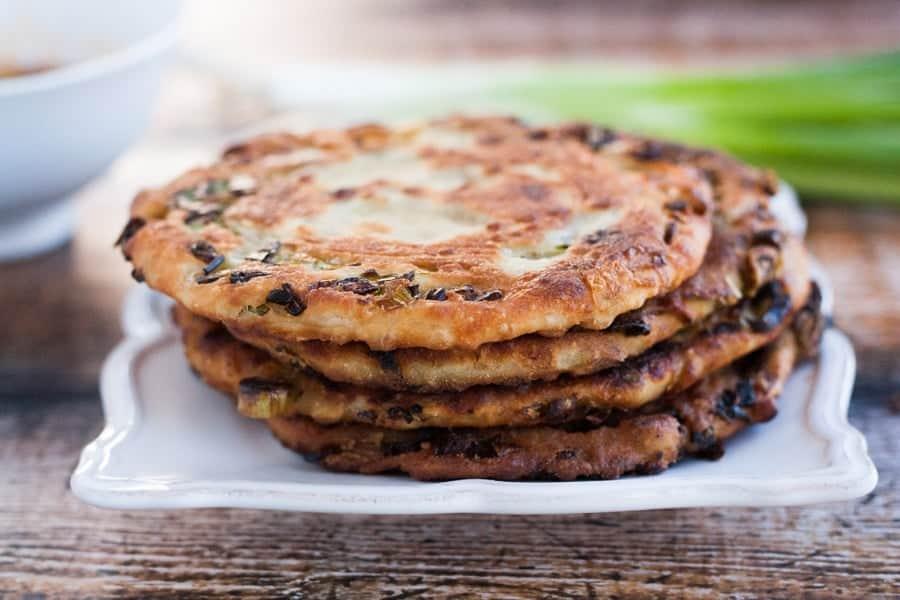 crispy scallion pancakes stacked on a serving platter