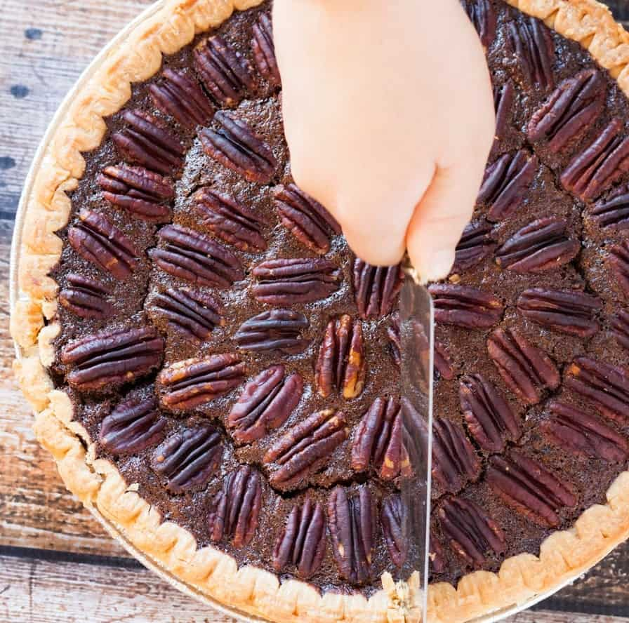 Chocolate pecan pie being sliced