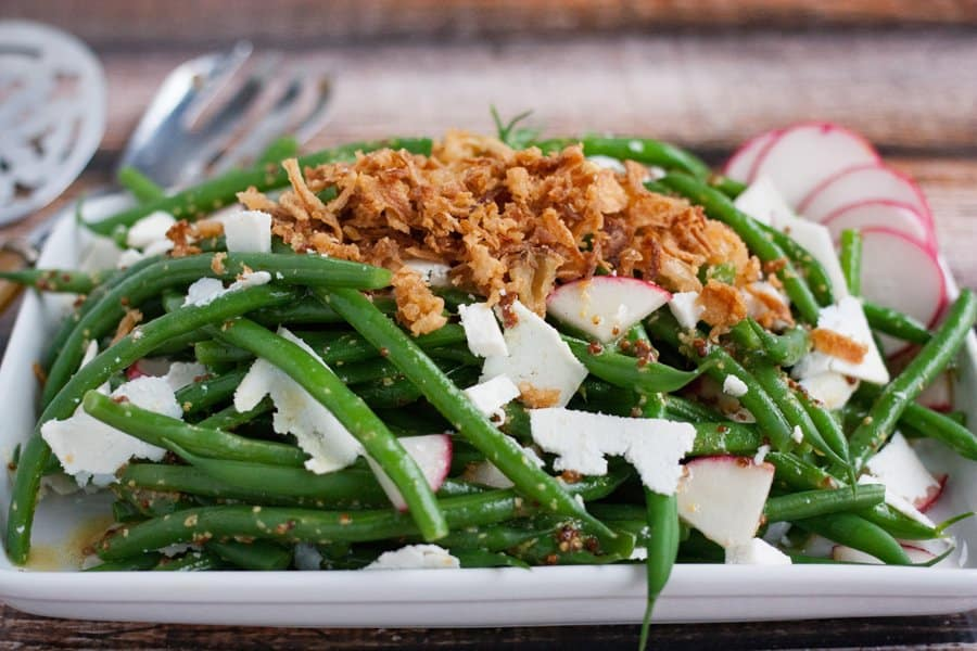 Grean bean salad with crispy fried onions on a serving plate