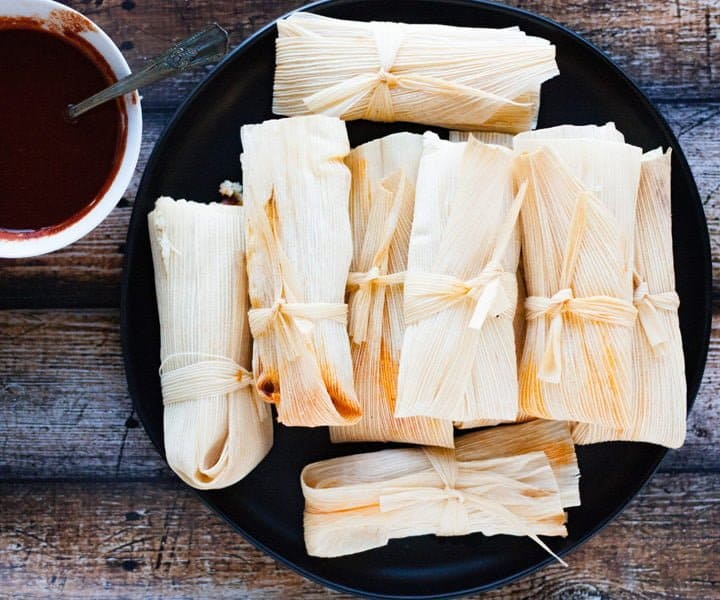 homemade tamales piled on a black plate with easy red chile sauce on the side