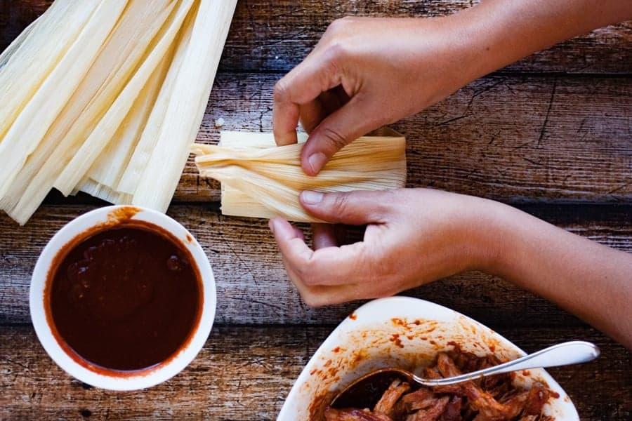folding corn husk around filled homemade tamales