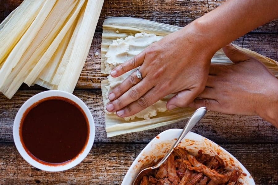 shaping tamale dough on corn husks