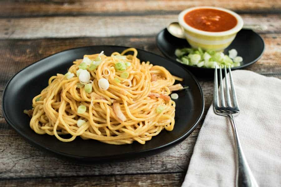 garlic noodles on a plate with hot sauce and scallions