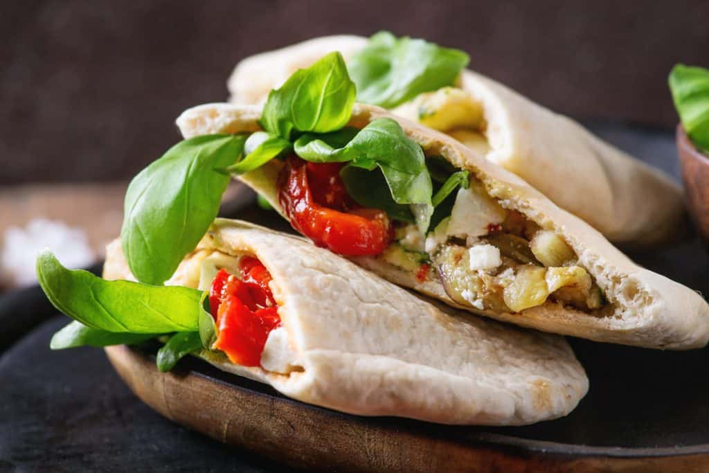 low angle shot of 2 halves of pita bread stuffed iwth eggplant, roasted pepper and fresh basil.