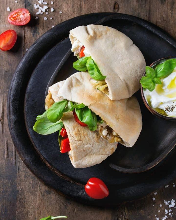 overhead shot of 2 halves of pita bread stuffed iwth eggplant, roasted pepper and fresh basil.