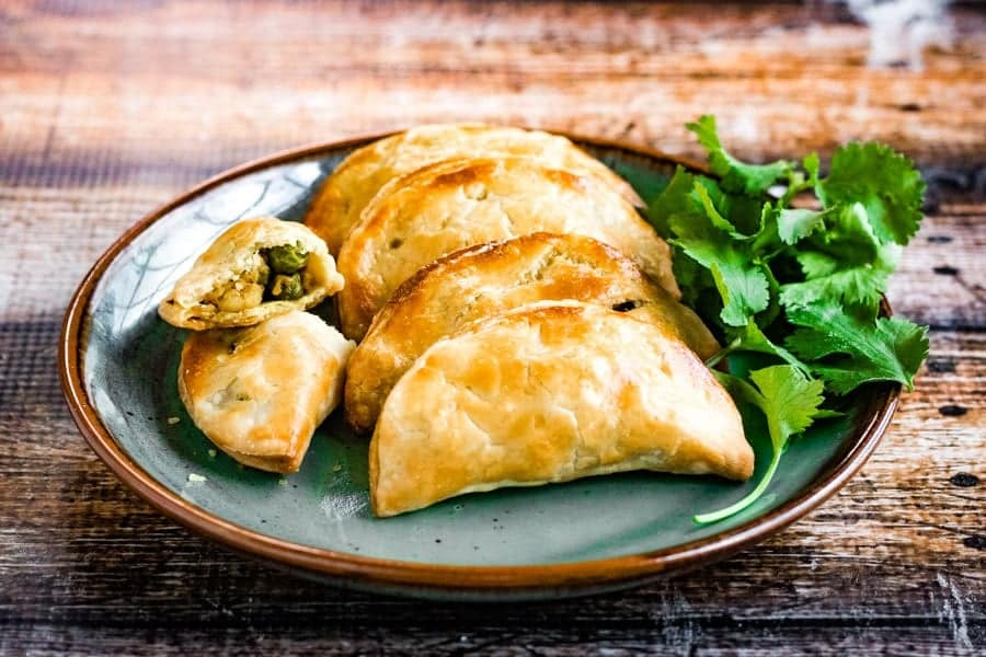 Thai curry puffs filled with ground chicken, potatoes, peas, onions, garlic and spices are a mouthwatering snack
