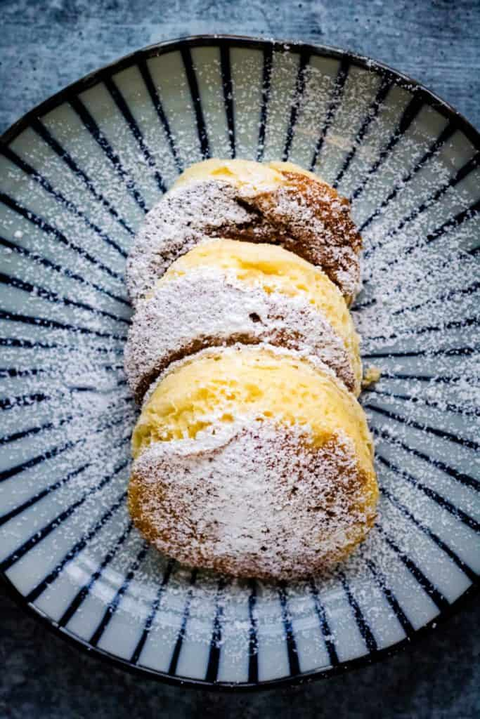 overhead shot of souffle pancakes dusted with powdered sugar on a pretty Japanese plate