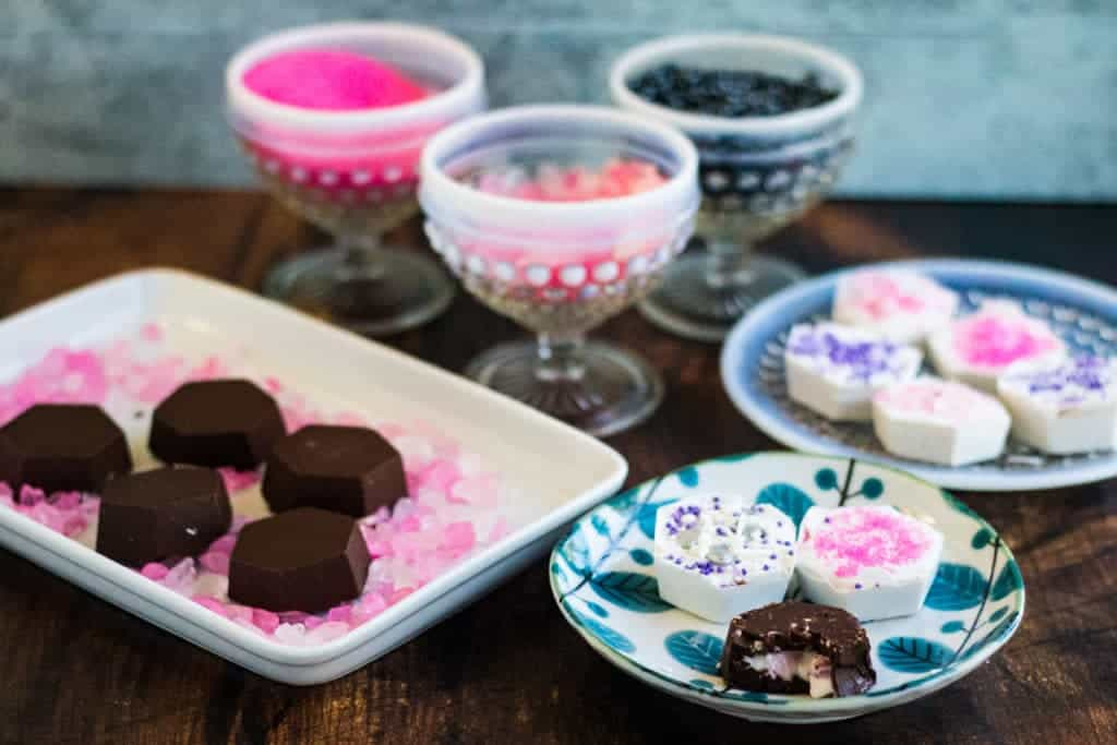 chocolate covered strawberry cheesecake bites on plates with sprinkles