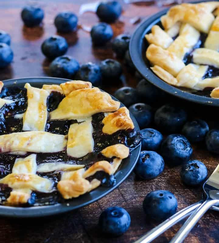 Mini blueberry pie with two forks and lots of fresh blueberries