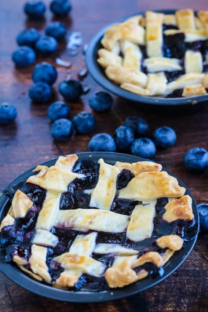 Mini blueberry pies shot from a low angle with fresh blueberries scattered around on a wood table