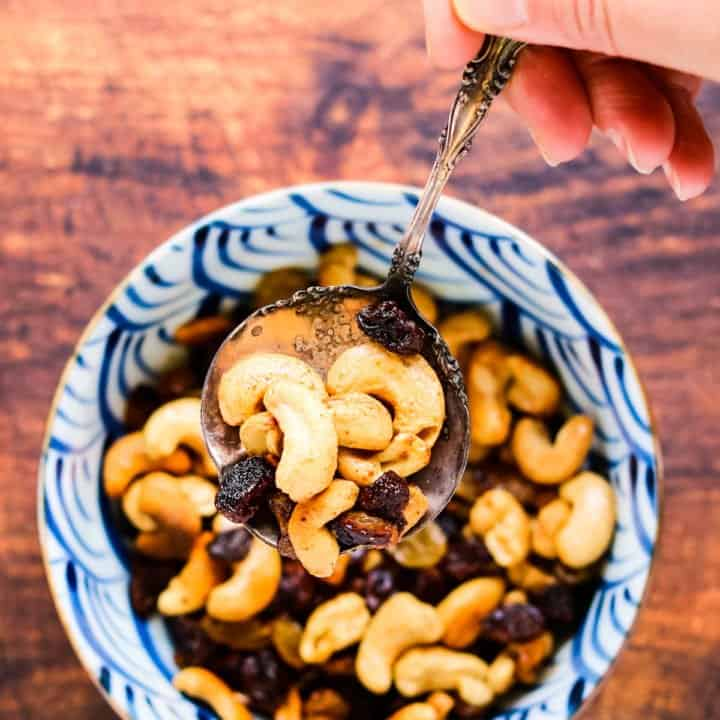 Caramelized cashews and raisins in a bowl with a silver spoon being lifted