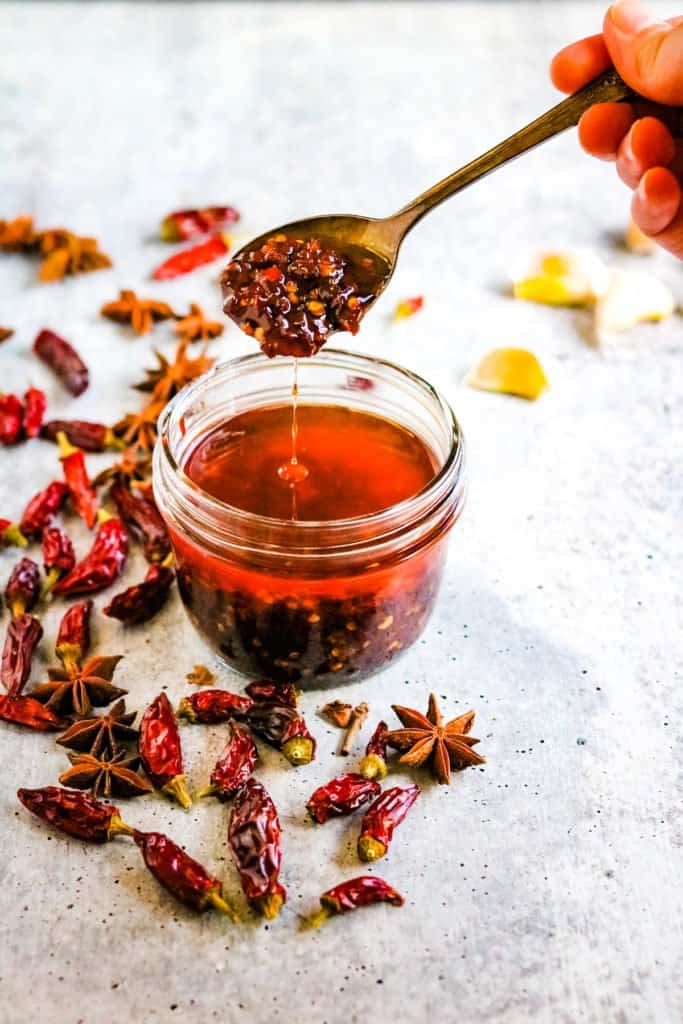 hot chili oil in a jar with the other ingredients that are used in this guide to how to make chili oil
