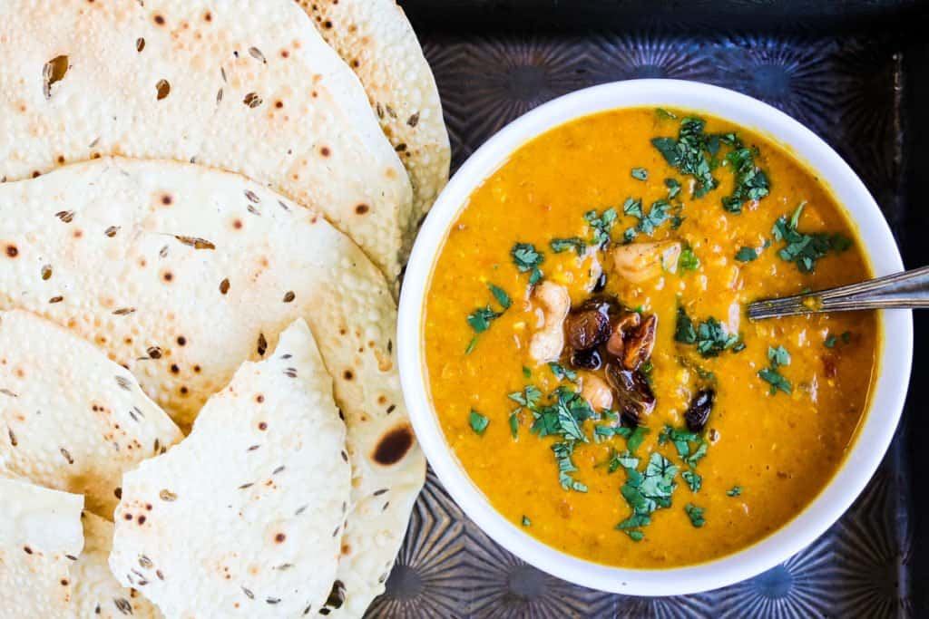 instant pot mulligatawnyb soup in a bowl with papadums on the side