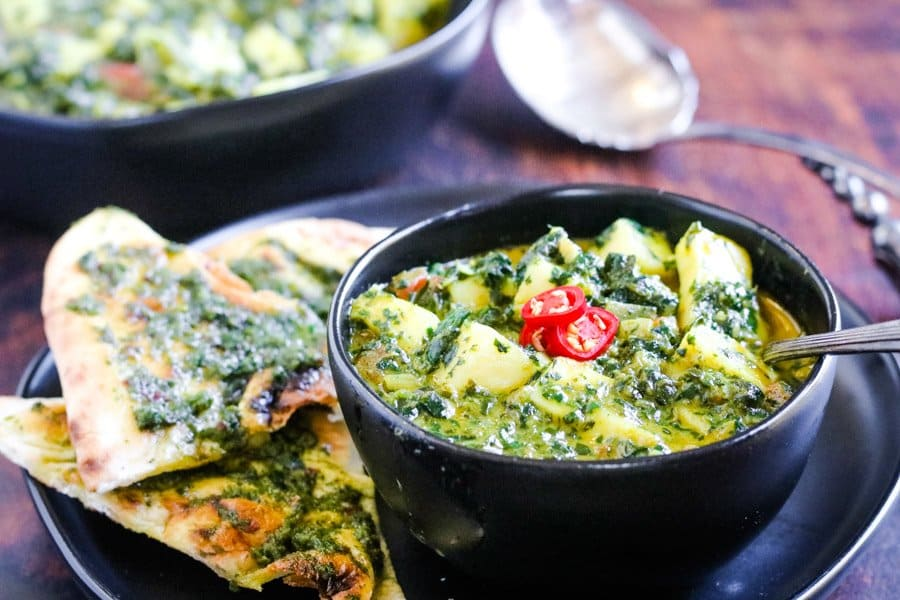 palak paneer in a bowl with a side of naan topped with herb chutney