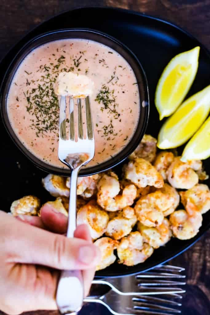 air fryer bang bang shrimp on a plate shot from overhead with a shrimp that has been dipped in the sauce on a fork