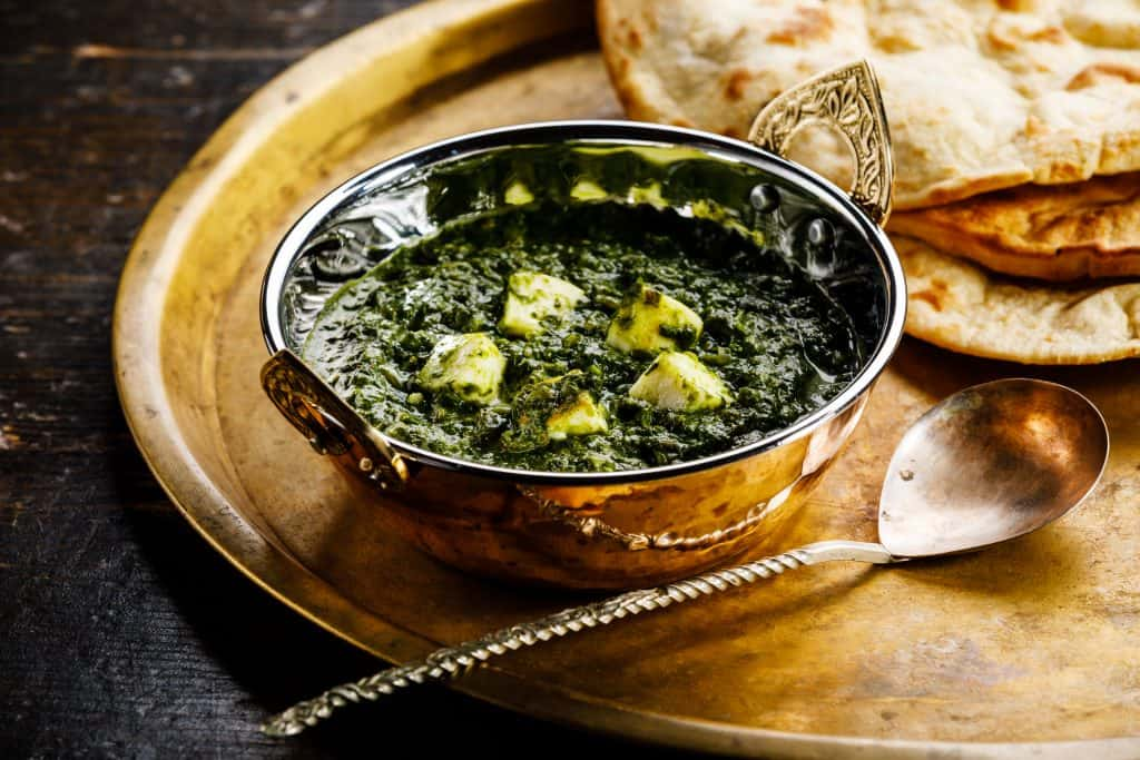 palak paneer in a metal bowl on a metal tray with a spoon and naan bread, shot from a low angle