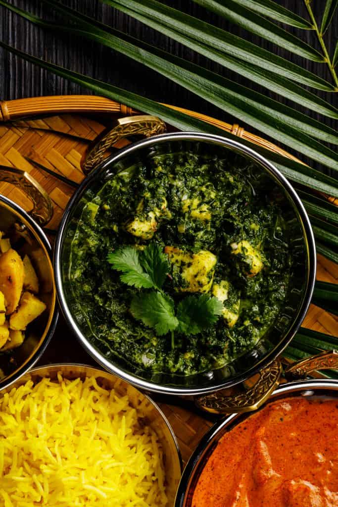 overhead shot of Indian cheese and spinach curry in a metal bowl. On the side are a bowl of yellow rice, a bowl of masala curry, and a palm frond