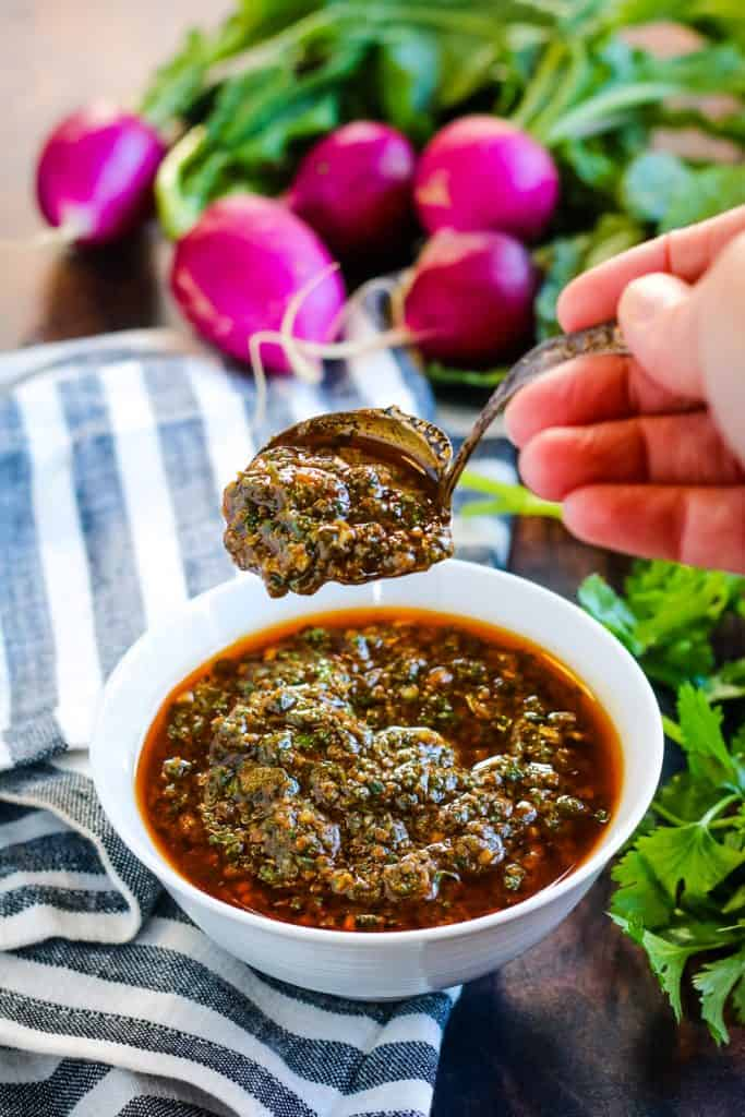 charmoula in a white bowl with a hand lifting a spoonful of the sauce