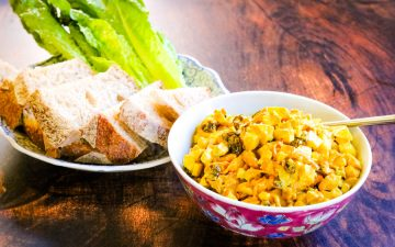 curried chicken salad with apples, raisins, and cashews in a bowl with a plate of bread and lettuce