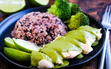 Thai green curry chicken on a plate with multi-grain purple rice, broccoli. and lime wedges