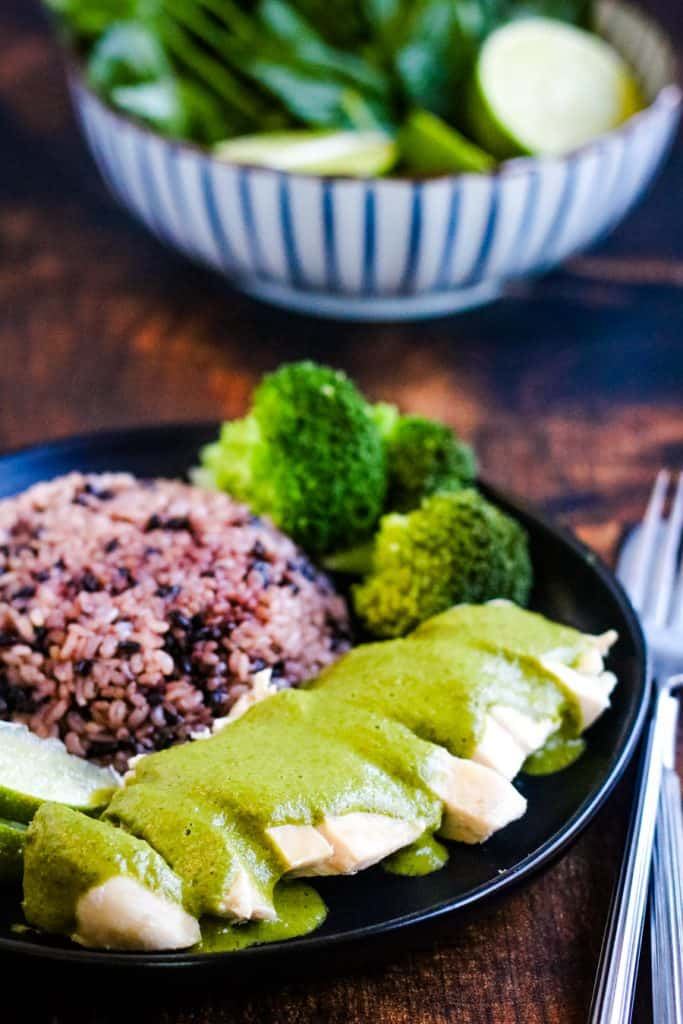 vertical shot of thai green curry chicken on a plate with purple rice and broccoli