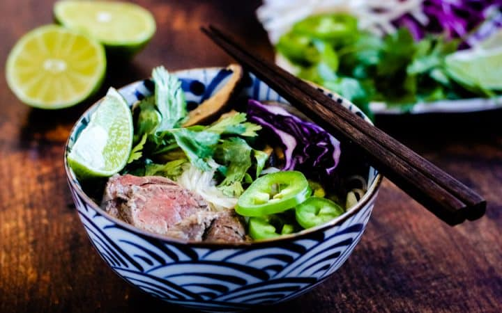 instant pot beef pho in a bowl garnished with cilantro, lime wedges, chile slices, and bean sprouts