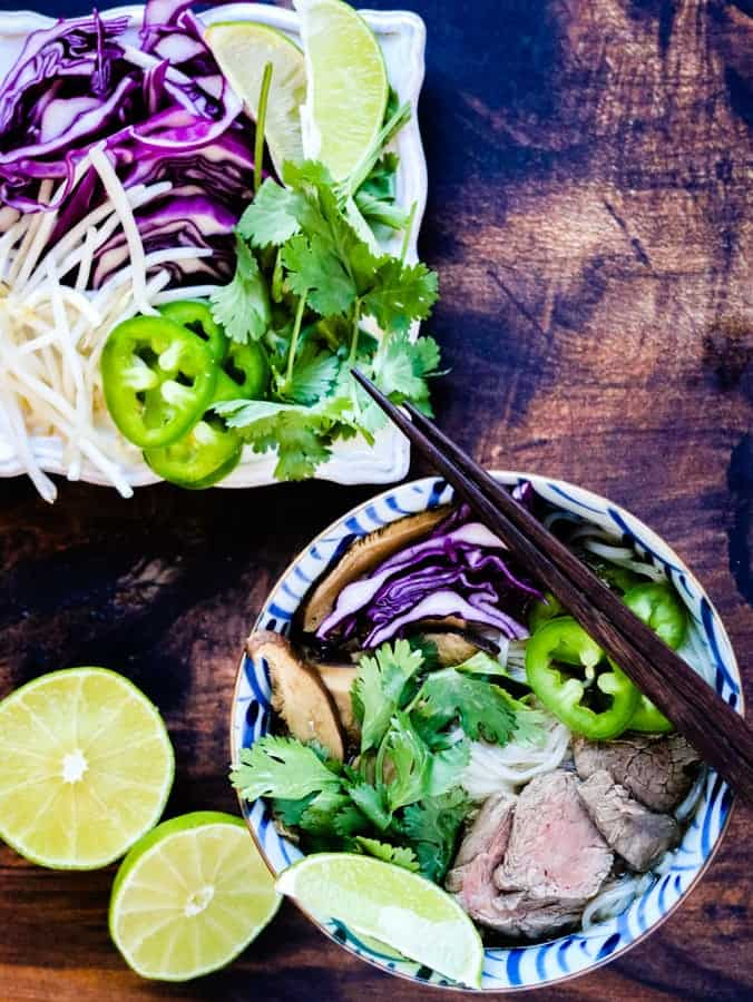 overhead shot of beef pho and garnishes