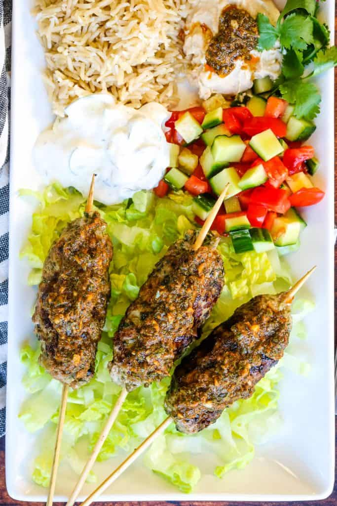lamb kofta shot from overhead with salads, rice, and dips