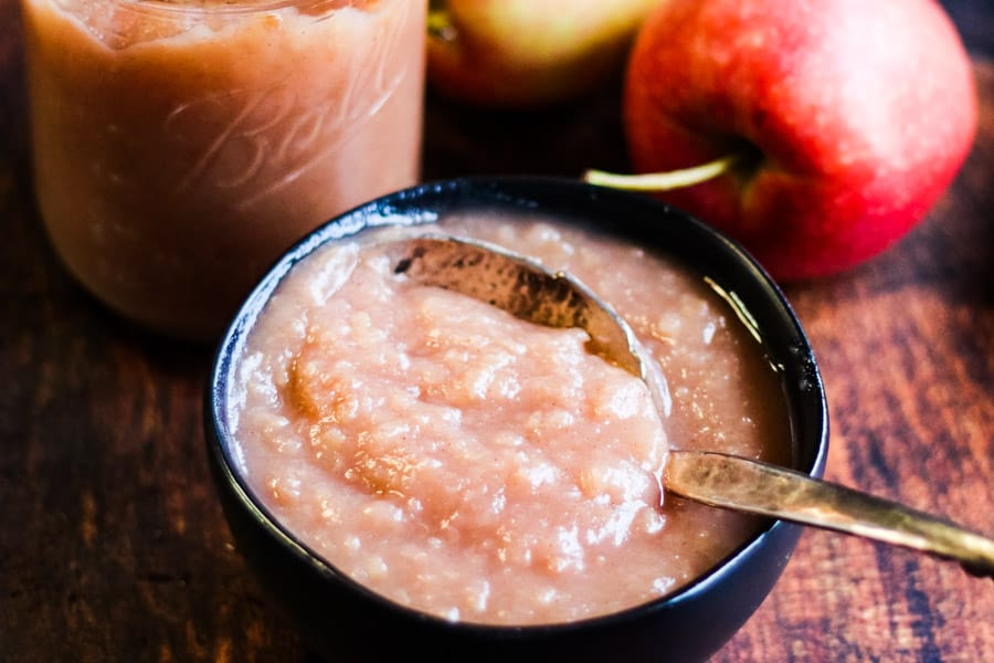 Instant pot applesauce in a bowl with a jar of appleasauce and some fresh apples