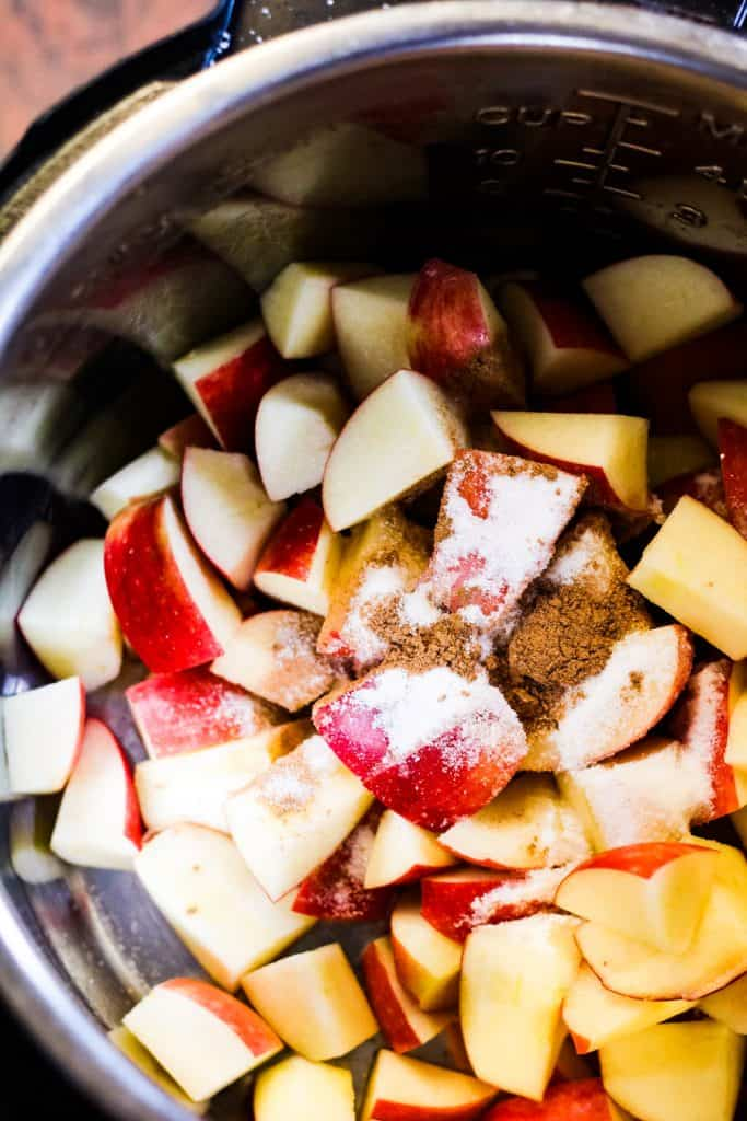 overhead shot of apples in the instant pot with sugar and cinnamon