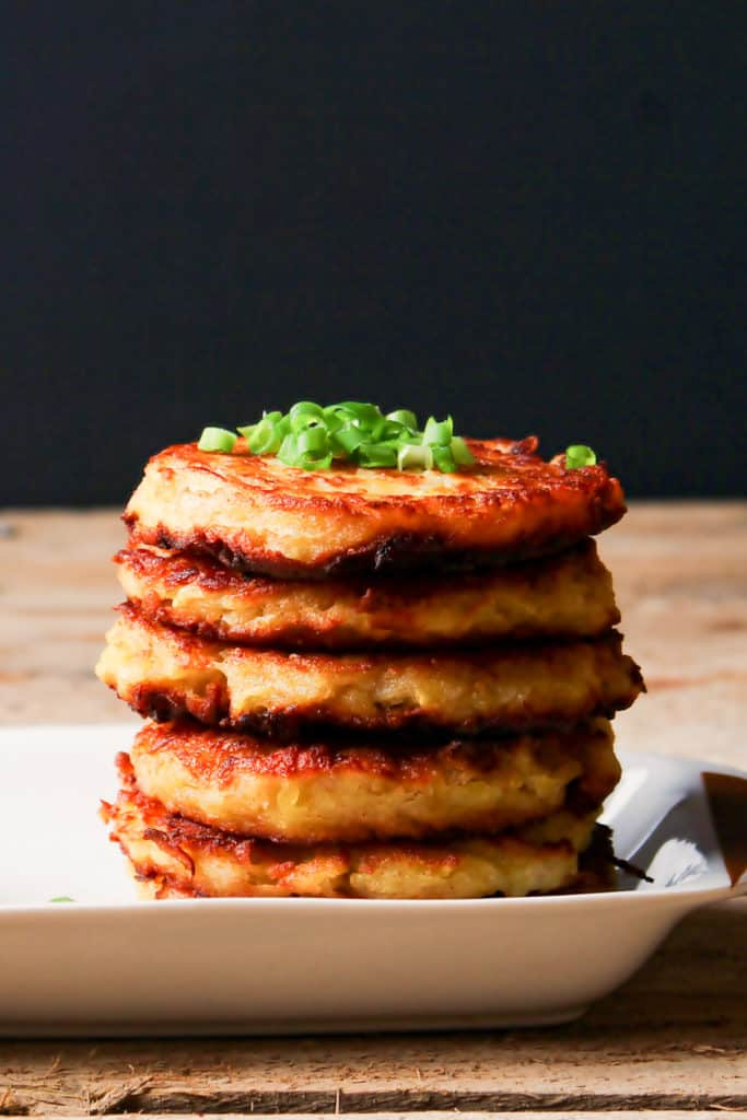 Low angle photo of a stack of 5 potato latkes on a white rectangular plate. Potato latkes are garnished with sliced green onions.