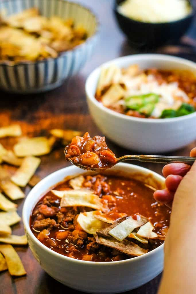 bowl of chili with a hand lifting a spoonful