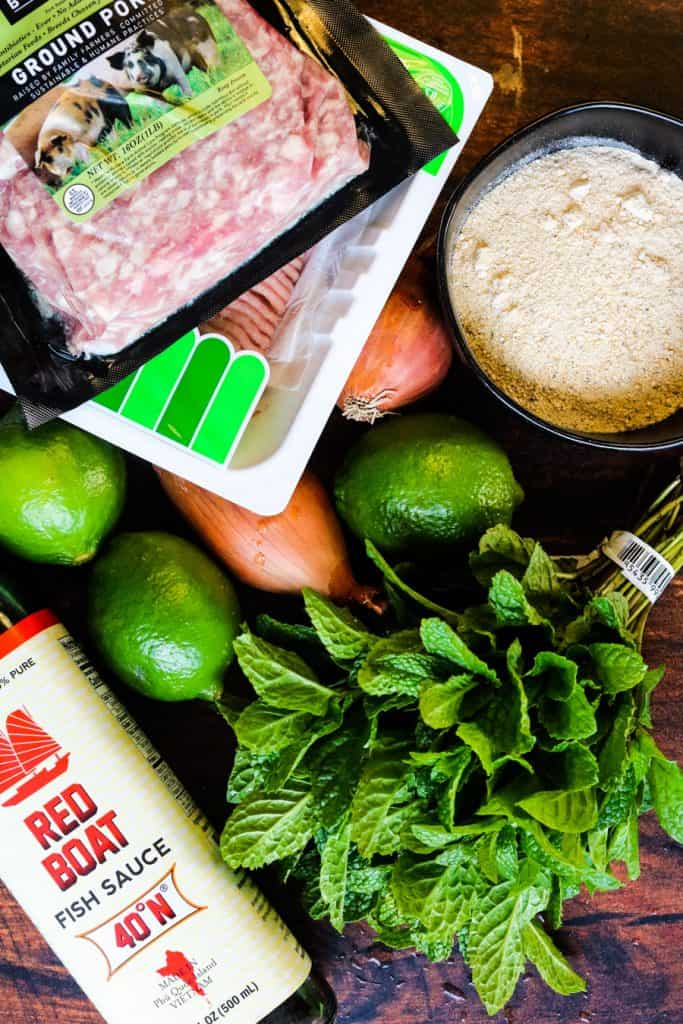 Ingredients for thai larb including ground meat, roasted rice powder, limes, shallots, fish sauce, and fresh mint