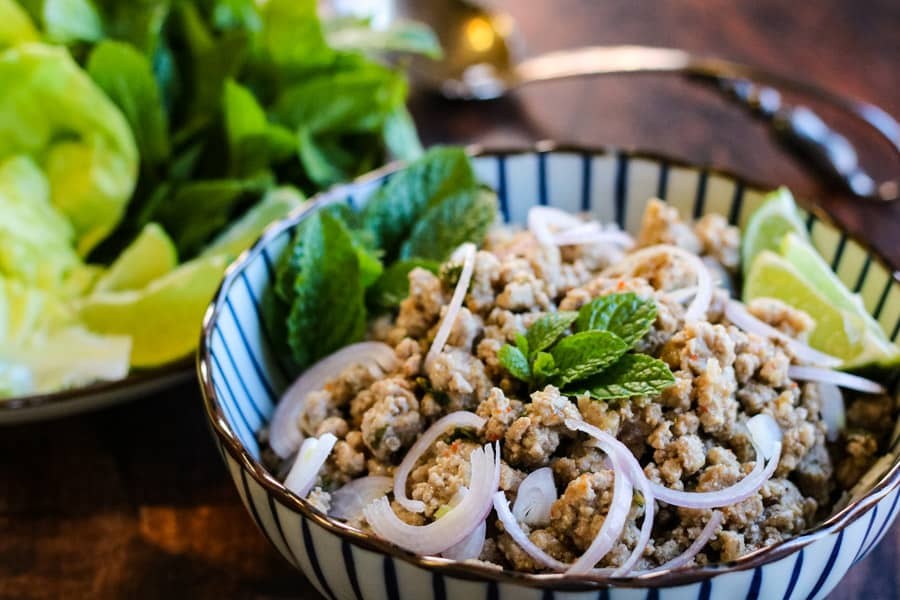 Landscape shot of thai larb in a blue and white serving bowl with fresh mint, lime wedges, sliced shallots, and lettuce leaves