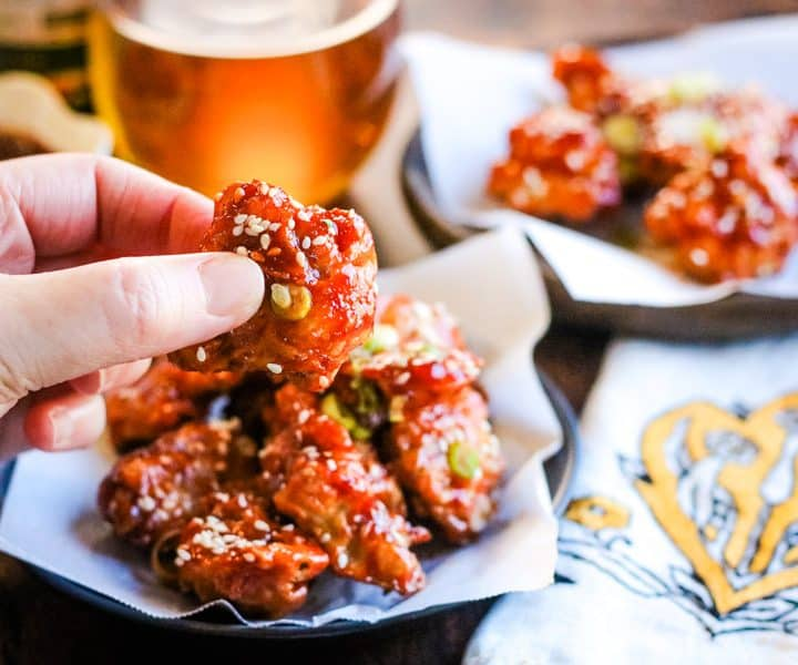 Korean fried chicken on a plate with a beer and someone holding a piece of the chicken in their fingers