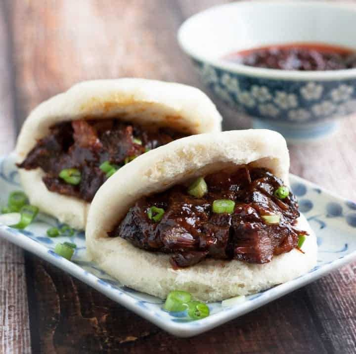 chinese steamed buns filled with char siu pork on a plate with scallion garnish