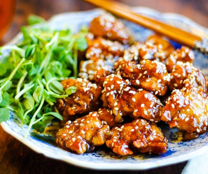 sesame chicken on a plate with pea shoots and chopsticks