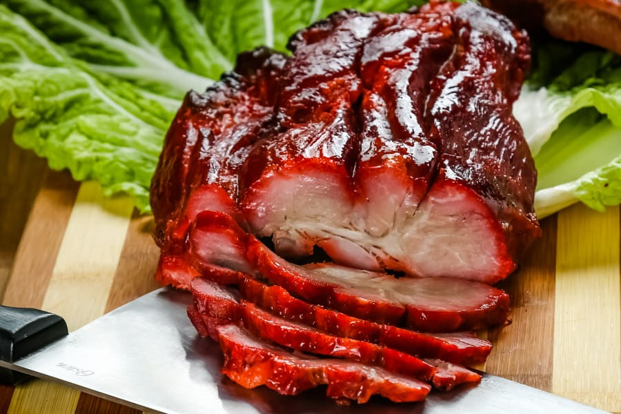 char siu pork sliced on a cutting board with leafy greens
