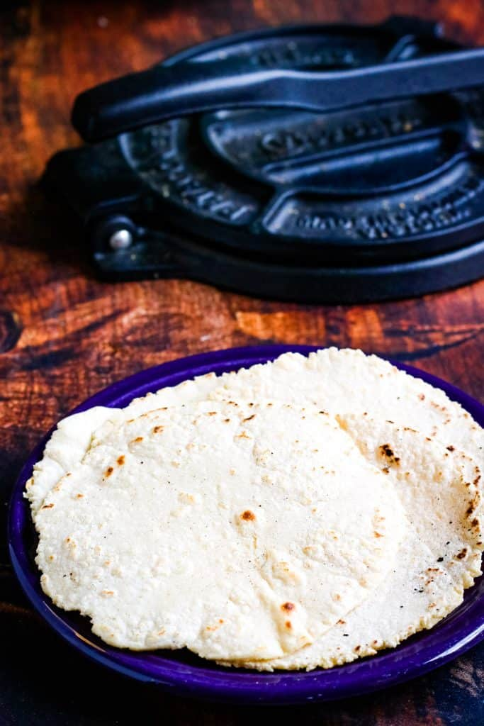 corn tortillas on a plate with tortilla press in the background