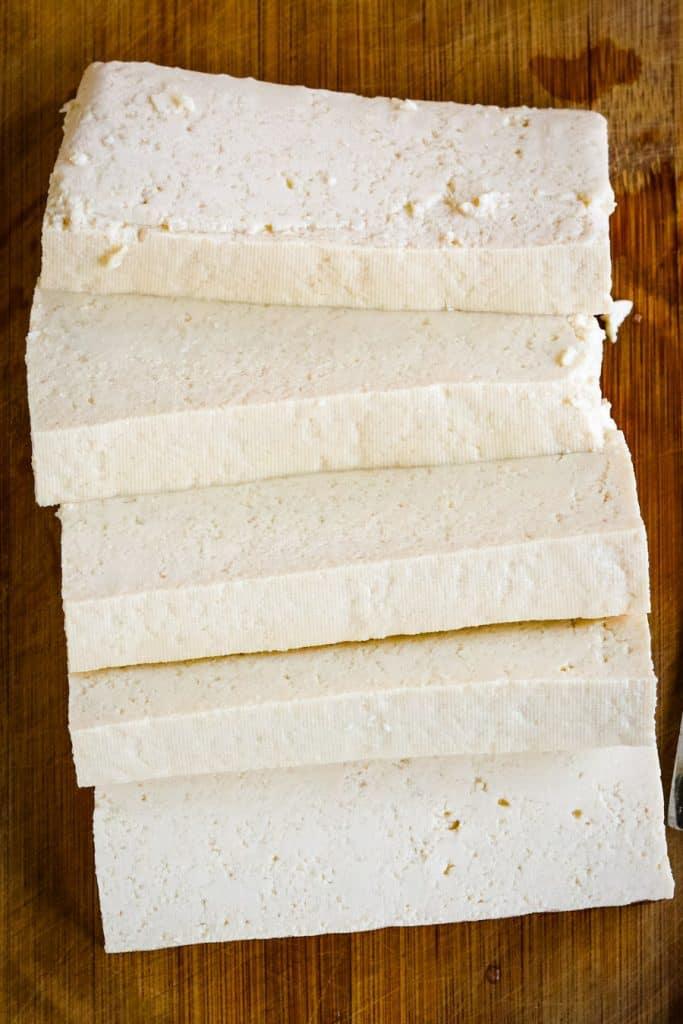 tofu cut into slabs on a cutting board