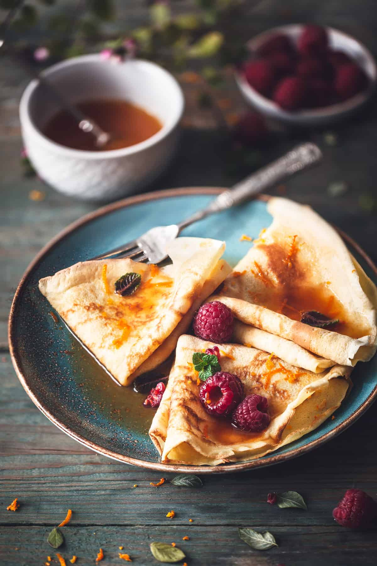 low angle photo of crepes on a blue plate with syrup. A bowl of raspberries is on the side